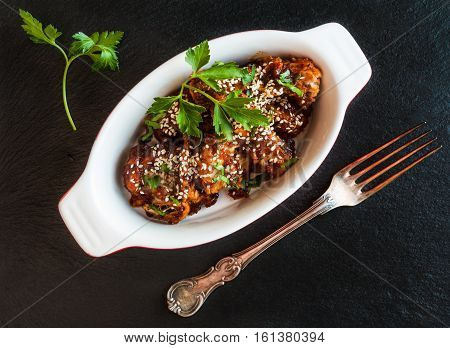 Glazed pork with homemade sauce made from onions garlic tomatoes mustard vinegar honey soy sauce and sesame seeds. Black stone background baking dish fresh parsley vintage fork.