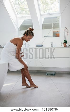 Woman Applying Moisturizer On Her Legs After Bath.