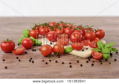 Scattered cherry tomatoes with leaves of basil on the wooden table.