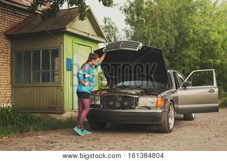 Girl from 1990's looking under hood of car