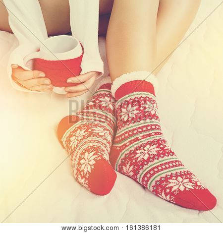 Young woman in Christmas pattern socks holding a mug with tea or coffee. Square format image, color filter applied, unrecognizable person.