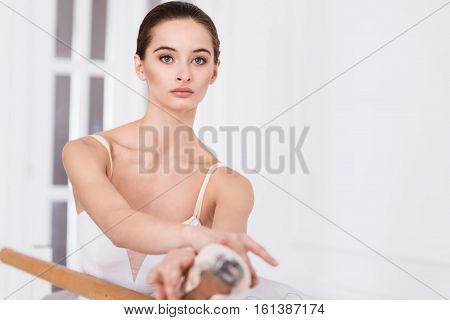 Important thoughts. Earnest adorable ballerina touching her leg with crossed arms while stretching her leg on the ballet bar, looking straight
