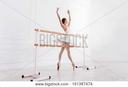Grace in motion. Classical dancer standing on tiptoes in semi position behind ballet bar holding both arms upwards while training