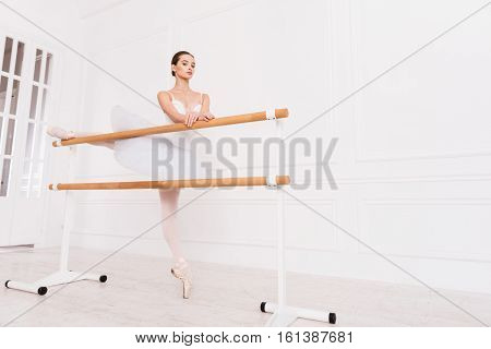 Be proud. Low angle picture of serious female wearing points and white leotard with fluffy skirt standing on tiptoes holding both arms crossed on the bar while looking at camera