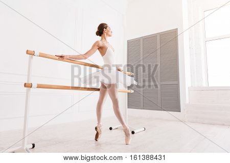 Train with pleasure. Slim classical dancer standing on tiptoes in semi position wearing points holding both arms on ballet bar