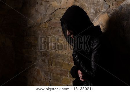 Disease. AIDS concept. Drug addict having depression while posing near brick wall on street. Drug addict having pain.