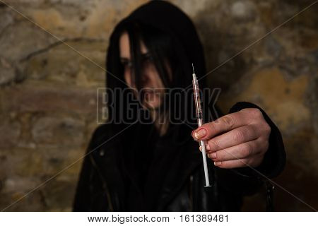 Disease. AIDS. HIV. Bad woman with syringe using drugs. Drug addict woman holding syringe with drugs in front of her.