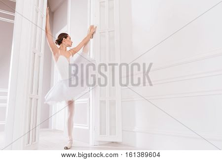 Feel tired. Elegant woman wearing white leotard with tutu touching her leg while doing stretching exercises