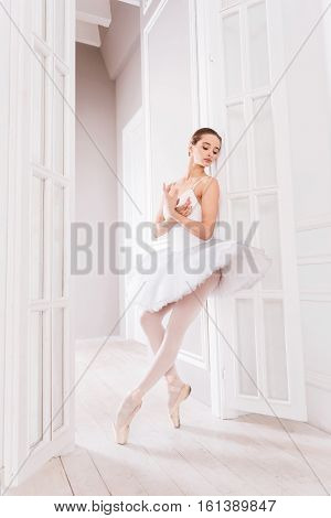 I am ready. Professional dancer crossing her arms on the chest looking sideways while standing on the tiptoes