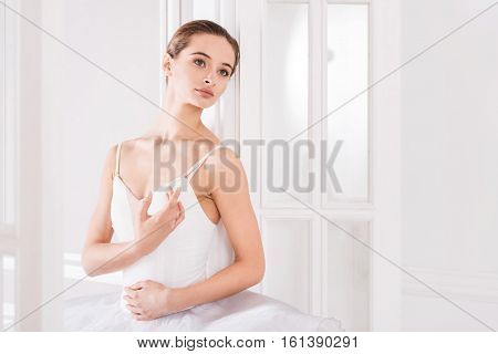 Look in future. Portrait of serious ballerina looking sideways holding her left arm on the stomach while standing against white background