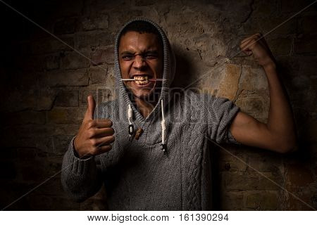 Drug addict man hooked on needle. Addiction, disease concept. Asian man with syringe in his mouth. Drugs concept.