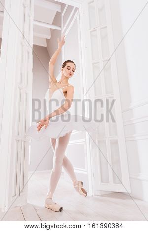 Classical position. Adorable young woman wearing white leotard with fluffy skirt holding her arm in the air while doing ballet positions