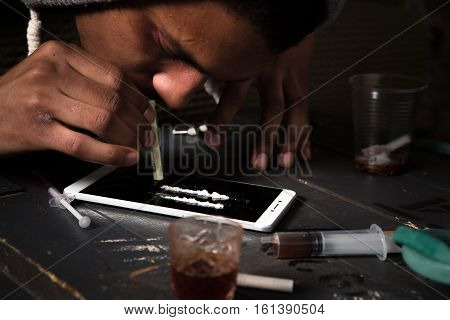 Disease concept. Drugs concept. Closeup picture of drug addict using drugs with help of mobile or smart phone. Drug addict man alone.
