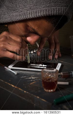 Closeup picture of drug addict using drugs with help of mobile or smart phone. Disease concept. Drugs concept.