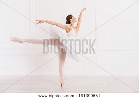 Ballet skills. Elegant ballerina looking aside wearing white leotard with tutu while posing in dance studio