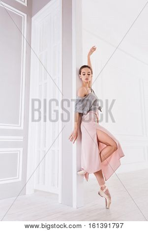 Stretch your body. Graceful ballet dancer wearing grey top over pink dress holding her shoulders bare staring head first