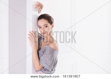 Be earnest. Graceful young ballerina wearing grey top keeping hands around her face posing in white room