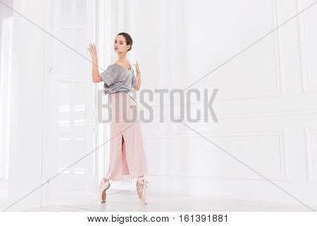Strong toes. Graceful ballet dancer holding white doors with both hands looking at camera while standing on tiptoes
