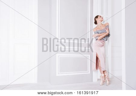 Excellent results. Tender slim ballerina wearing grey top over pink dress keeping hands crossed on the chest while standing on tiptoes