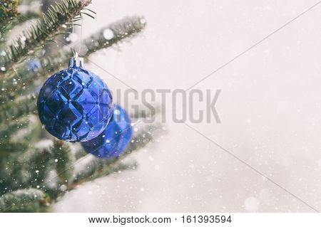 Close-up of blue Christmas balls during snowstorm with copy space
