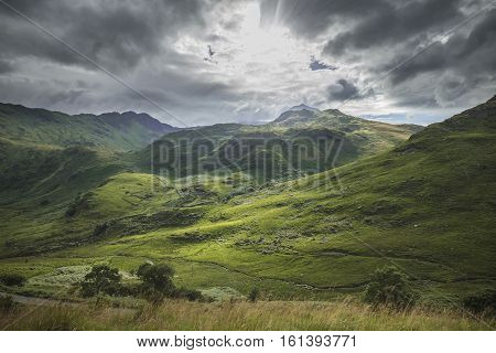 Sun Rays Falling onto Green Slopes of Snowdonia Mountains in North Wales