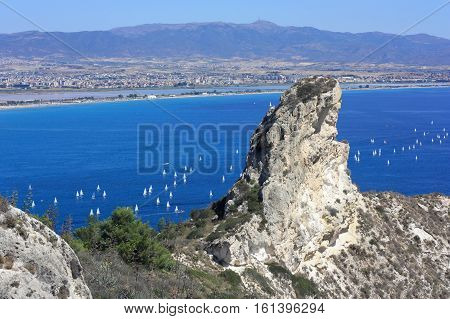 Aerial view on the rock Sella del Diavolo -the Devil's Saddle Cagliari famous beach il Poetto and the Golf of Cagliari with white sailboats in Sardinia Italy.