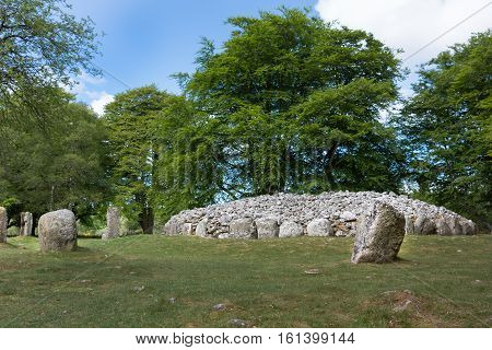 Inverness Scotland - June 2 2012: The menhir stone circle and grave site heap of gray stones at prehistoric Clava Cairns. Surrounded by green trees grassy field and white clouds in blue sky.