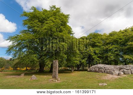 Inverness Scotland - June 2 2012: Wide shot of the menhir stone circle and grave site heap of gray stones at prehistoric Clava Cairns. Surrounded by green trees grassy field and white clouds in blue sky.