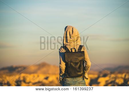 Young woman traveller wearing hoodie and backpack watching sunrise in the mountains over Goreme, Cappadocia, Central Turkey
