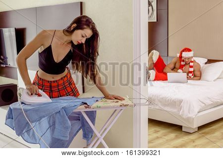 Girlfriend of Santa Claus ironing clothes at home, Santa taking rest on his bed with laptop