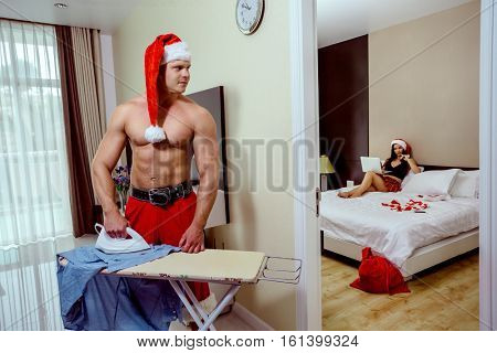 Santa ironing clothes at home, girlfriend of Santa Claus taking rest on the bed with laptop