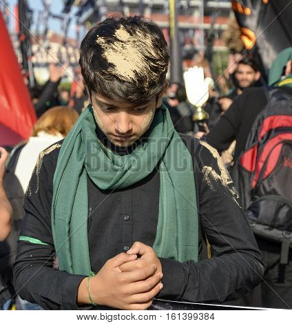 Istanbul Turkey - October 11 2016: Turkish Shia children takes part in an Ashura parade in Istanbul's district of Kucukcekmece. A young man mood chronology to adapt to his hair and clothes muddy. Caferis take part in a mourning procession marking the day