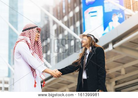Business Success Concept. Asian Muslim Businessman And Engineer Woman Making Handshake Or Holding Ha