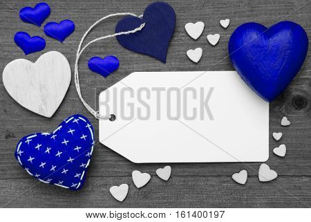 Label With Copy Space For Advertisement. Blue Textile Hearts On Wooden Gray Background. Retro Or Vintage Style. Black And White Image With Colored Hot Spot.