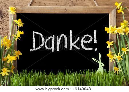 Blackboard With German Text Danke Means Thank You. Spring Flowers Nacissus Or Daffodil With Grass And Easter Bunny. Rustic Aged Wooden Background.