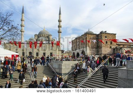 Istanbul Turkey - March 29 2013: New Mosque (Yeni Cami) People and pigeons around the courtyard. On the right is the historic building with the entrance to the Spice market - Eminonu (Egyptian Bazaar). It is situated on the Golden Horn at the southern end