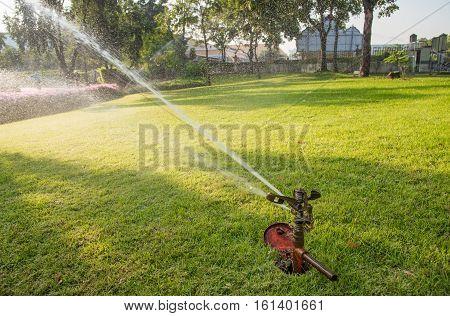 Sprinkler watering on green grass floor in the park
