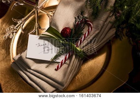 Holiday card on Christmas Celebration Place setting with Thank you words written by hand on white card with candy cane and crystal ornament golden colors for expressing holiday gratitude messages to friends, family and business partners with personal touc