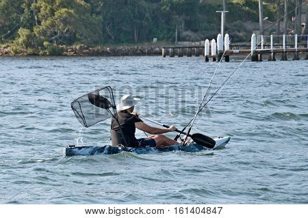 Man fishing in sea water from a kayak (AKA Yak) with all the feshing gear ( rods net & anchor). Photographed in Gosford Broadwater New South Wales Australia.