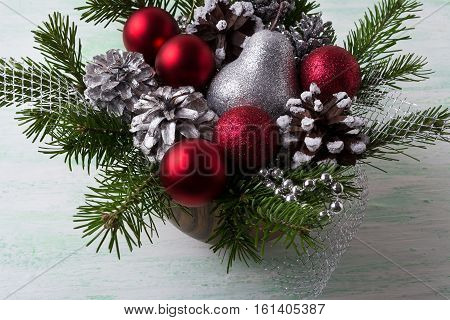 Christmas arrangement with red baubles and decorated pine cones. Christmas decoration with fir branches and red ornaments. Christmas silver glitter table centerpiece.