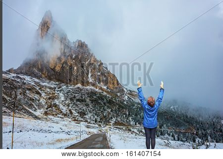 Dolomites in Northern Italy. First snow on mountain passes Giau. Elderly woman in awe of the beauty of nature