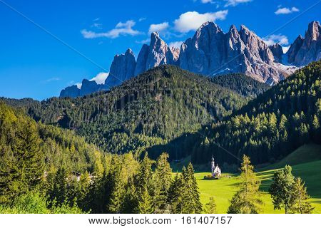 Dolomites, Tirol. Sunny day. Rocky peaks and forested mountains surrounded by green Alpine meadows. The symbol of the valley Val di Funes - church of Santa Maddalena