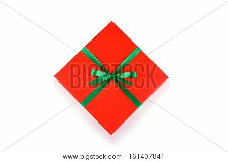 Top view of red gift box with green ribbon and bow isolated on white background