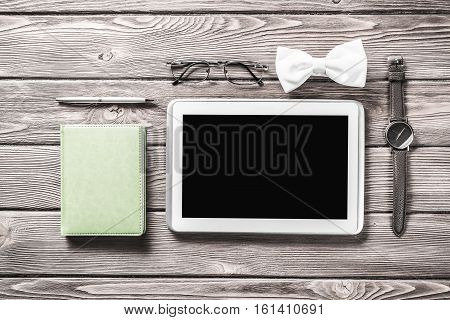Tablet pc computer wallet eyeglasses bowtie and wristwatch on table