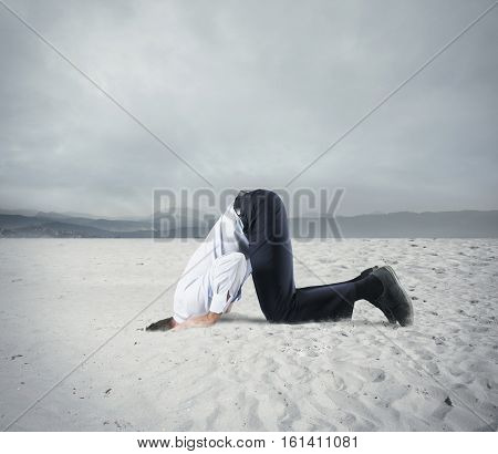 Afraid businessman hide his head under the ground like an ostrich. Fear of crisis concept