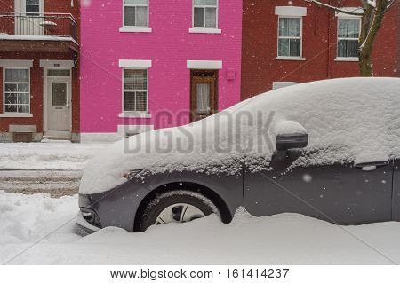 Montreal CA 12 December 2016. Car covered with snow in front of pink traditional house during snow storm