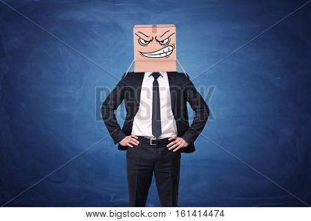 Businessman is wearing cardboard box with drawn angry face on his head on blue chalkboard background . Anonymous person. Aggressive marketing strategies. Business issues.
