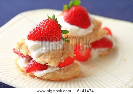Miniature strawberry shortcakes with whipped cream and fresh berries on a white dish