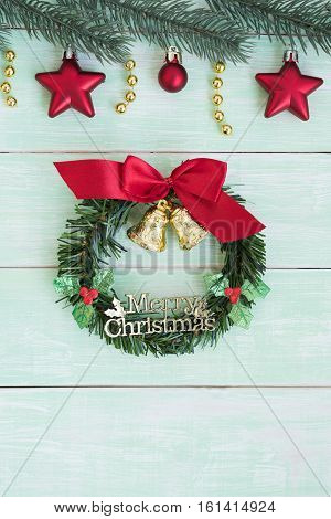 Christmas wreath with golden bells and red ribbon bow and fir branch decoration with baubles on green vintage background flat lay with copy space