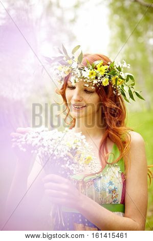 Red-haired girl in flower crown holding wildflowers